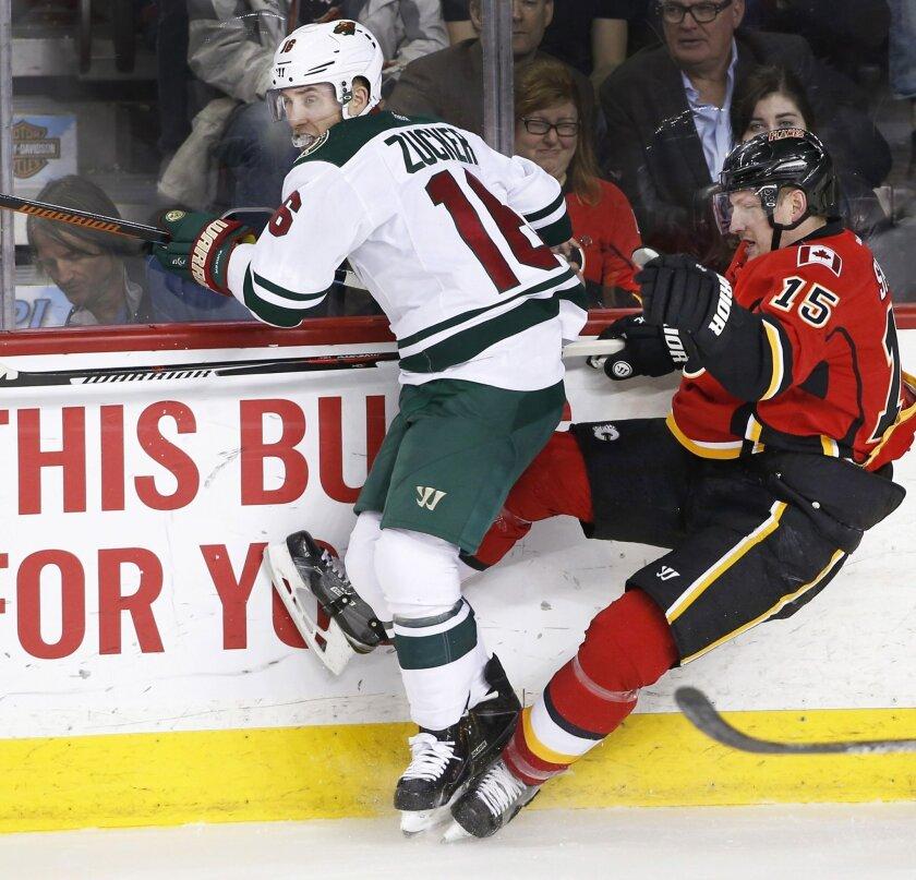 Minnesota Wild's Jason Zucker (16) checks Calgary Flames' Ladislav Smid, from the Czech Republic, during the first period of an NHL hockey game Wednesday, Feb. 17, 2016, in Calgary, Alberta. (Larry MacDougal/The Canadian Press via AP)