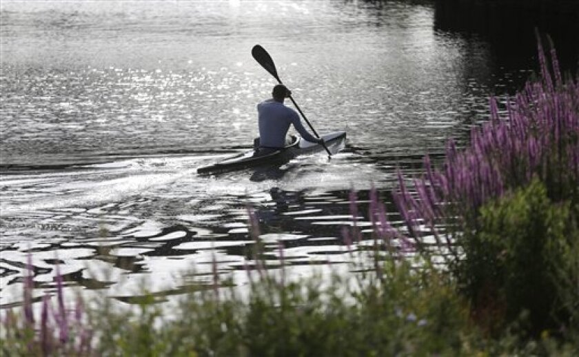 A kayaker passes under a bridge during training in Eton Dorney, near Windsor, England, at the 2012 Summer Olympics, Friday, Aug. 3, 2012. (AP Photo/Chris Carlson)