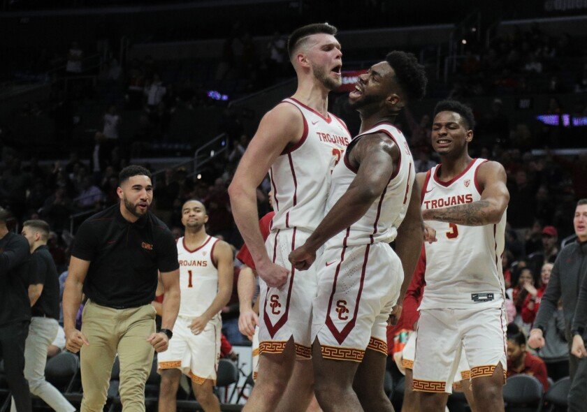 USC guard Daniel Utomi (4) celebrates with forward Nick Rakocevic after scoring late in the game against LSU on Dec. 21, 2019, at Staples Center.