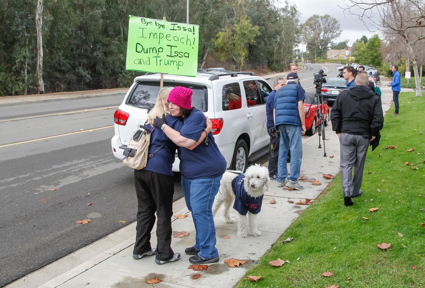 Linda Breen (left) hugs Lauren Kornit with her dog Manhattan before the start of rally celebrating Congressman Darrell Issa's announcement he will not seek re-election.