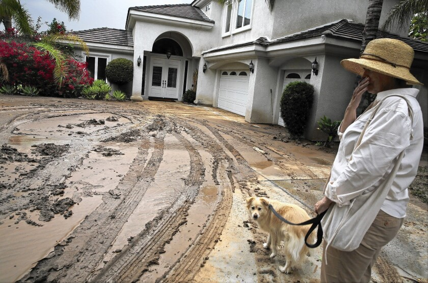Janette Johnson looks at the mud covered driveway of her home in Riverside.