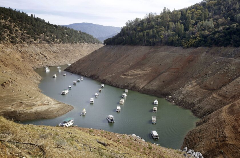 FILE - In this Thursday, Oct. 30, 2014, file photo, houseboats float in the drought-lowered waters of Oroville Lake near Oroville, Calif. Gov. Jerry Brown on Wednesday April 1, 2015 ordered sweeping and unprecedented measures to save water in California. Surveyors on Wednesday found the lowest snow level in the Sierra Nevada snowpack in 65 years of record-keeping, marking a fourth consecutive year of vanishing snow that California depends on to melt into rivers and replenish reservoirs. (AP Photo/Rich Pedroncelli, File)