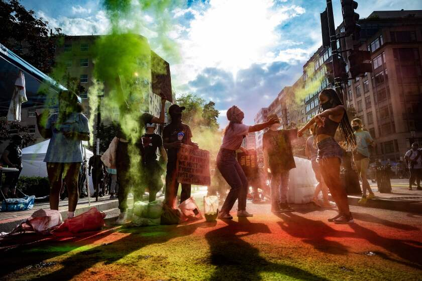 People gather for a march as colorful powder falls on the crowd