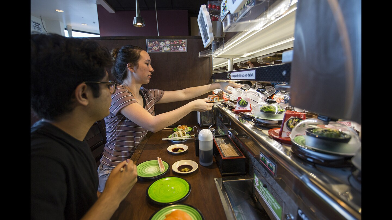 Taher Rahman, 19, left, and Cari Webb, 18, eat at Kula Revolving Sushi Bar at Diamond Jamboree on Friday, June 16.