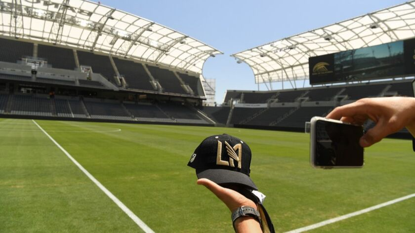 LOS ANGELES, CALIFORNIA APRIL 18, 2018-A fan holds a hat for a picture inside the LAFC soccer stadiu
