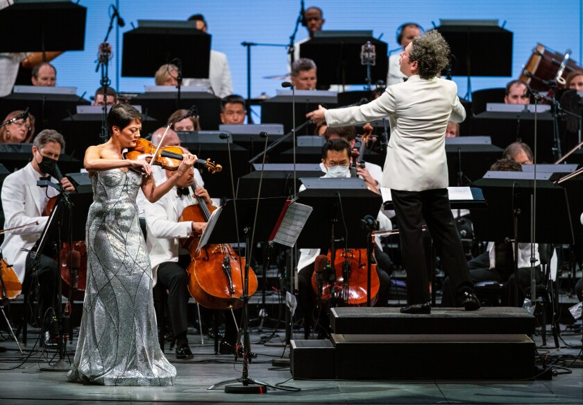 A woman in a silver-colored dress plays violin as a man conducts and orchestra
