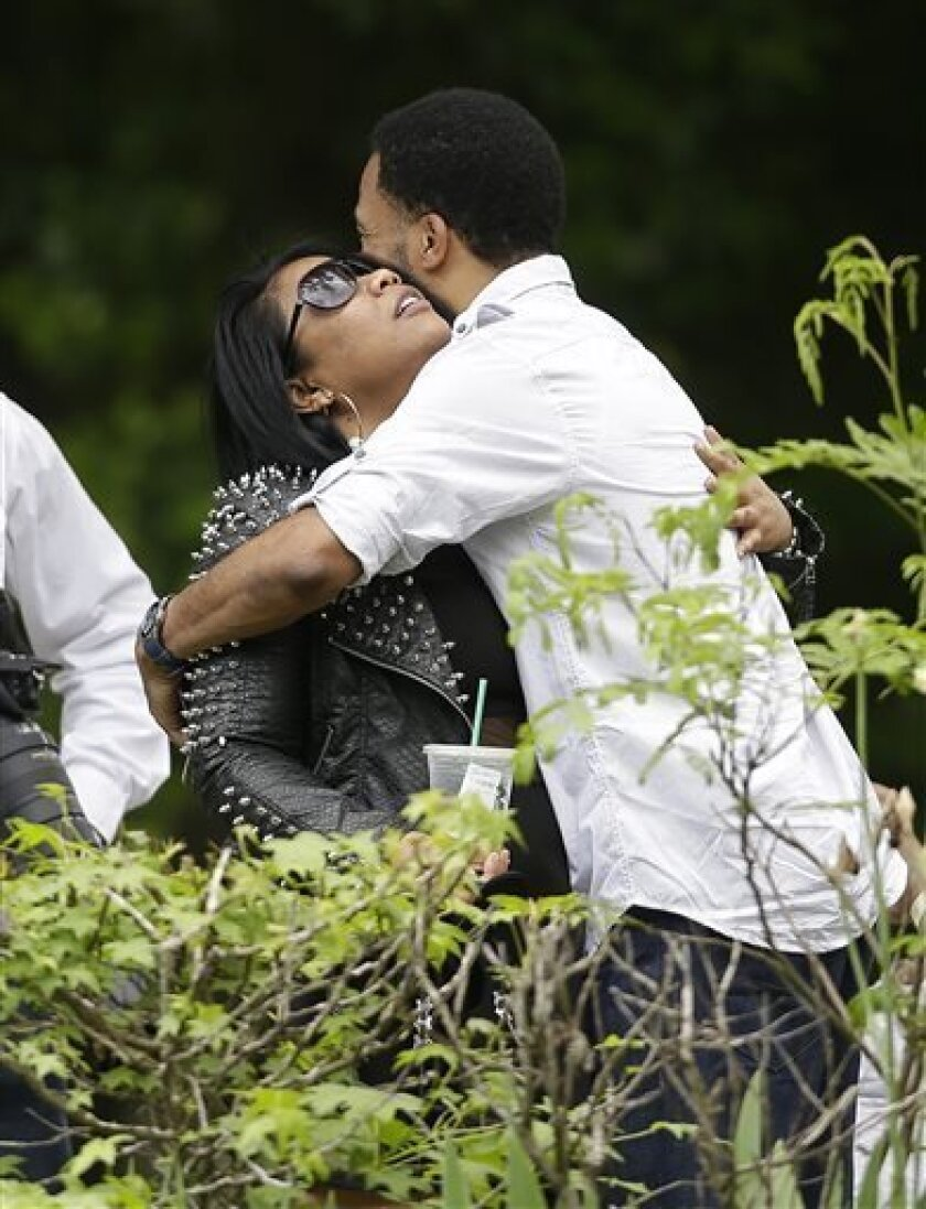 Mourners embrace outside a viewing for music artist Chris Kelly, Wednesday, May 8, 2013, in Atlanta. Kelly, who was part of the duo Kris Kross, died last Wednesday. He was 34. (AP Photo/John Bazemore)