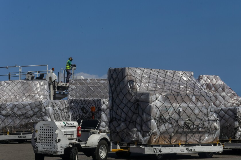 Workers at a Venezuela airport unload humanitarian aid from China on March 28, 2020.