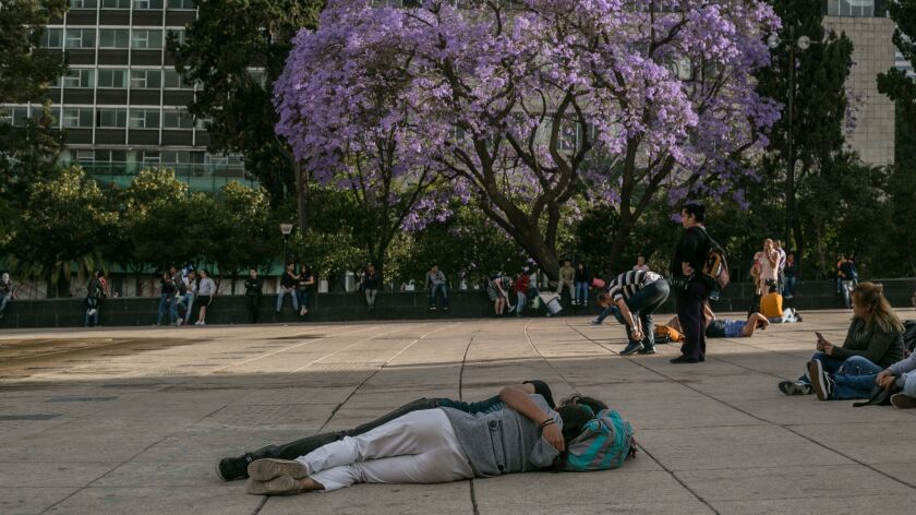 March 22, 2019 - A couple rests in an embrace in front of the Revolution monument in Mexico City. Th
