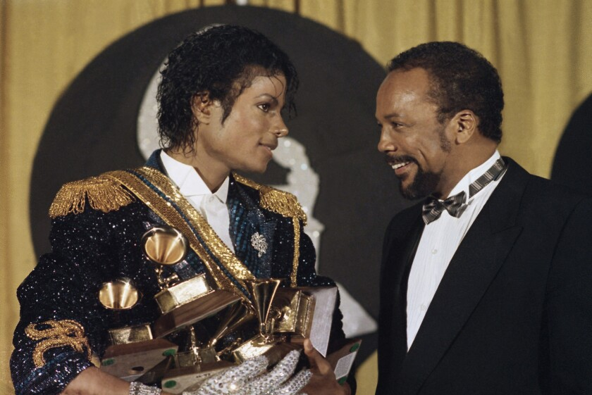 Michael Jackson is shown in 1984 holding his many awards as he speaks with Quincy Jones at the Grammy Awards. The year before, David Bowie put MTV on the spot for featuring so few black artists.