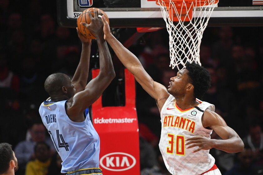 Atlanta Hawks center Damian Jones (30) defends against a shot by Memphis Grizzlies center Gorgui Dieng during the first half of an NBA basketball game Monday, March 2, 2020, in Atlanta. (AP Photo/John Amis)