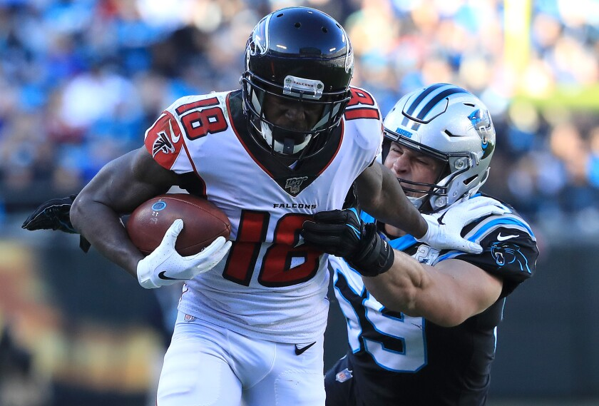 Falcons receiver Calvin Ridley is tackled by Panthers linebacker Luke Kuechly during a game Nov. 17 at Bank of America Stadium.