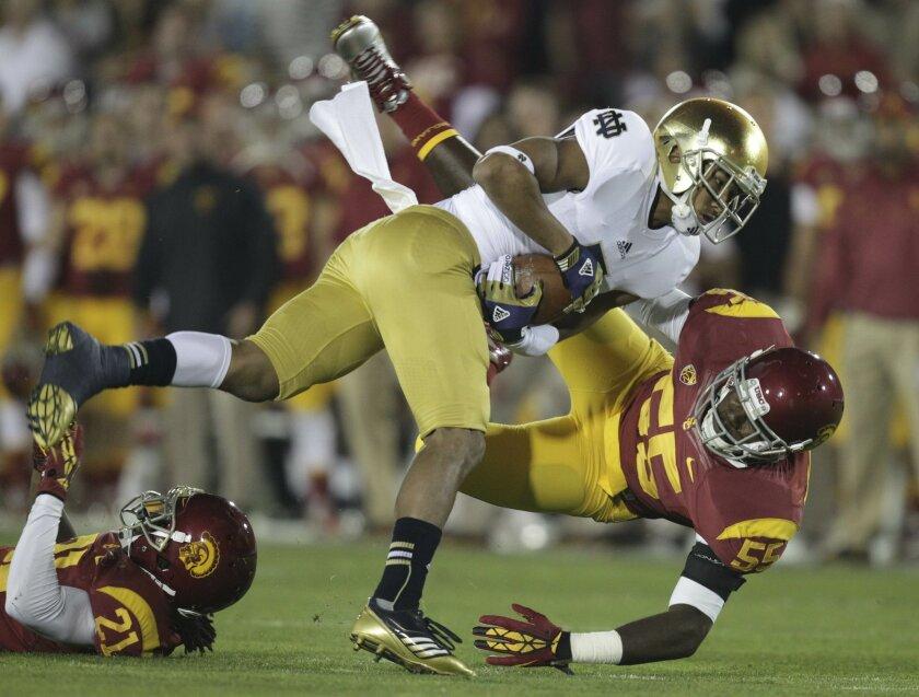 Notre Dame TJ Jones is hauled down by USC's Lamar Dawson. Linebacker Dawson was involved in a National Collegiate Athletic Association case.