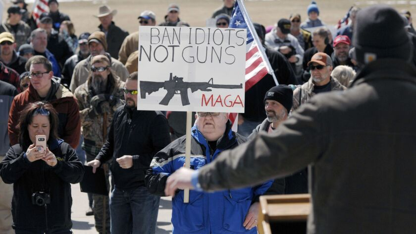 Steve Langlie, center, of Bismarck, North Dakota, holds a sign while listening to a speaker at the A