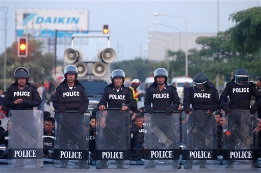 Thai riot police officers form a line on a highway as rubber farmers block on the other end during a protest in Surat Thani province, southern Thailand Tuesday, Sept. 3, 2013. At least 12,000 rubber farmers have staged protests and blocked another road in Thailand's south to try to force the government to boost declining rubber prices. (AP Photo/Sumeth Panpetch)