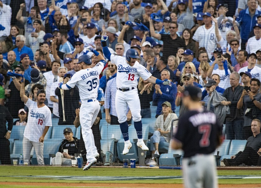 Dodgers first baseman Max Muncy (13) celebrates with on-deck batter Cody Bellinger (35) after Muncy hit a 2-run homer off the Washington Nationals in the first inning of Game 5 of the NLDS at Dodger Stadium on Oct. 9, 2019.