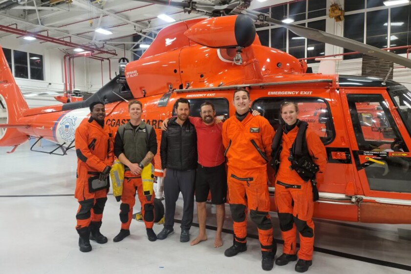 In this photo provided by the U.S. Coast Guard, kayaker Cyril Derreumaux, in shorts, poses with the Coast Guard helicopter crew that rescued him off the California coast in San Francisco on Saturday, June 5, 2021. A kayaker hoping to paddle solo from California to Hawaii was rescued six days after he set out by a U.S. Coast Guard helicopter amid rough seas and high winds. Cyril Derreumaux endured several problems with his 23-foot (7-meter) kayak, but when he lost his sea anchor he said he knew he had to cut his adventure short. (U.S. Coast Guard via AP)