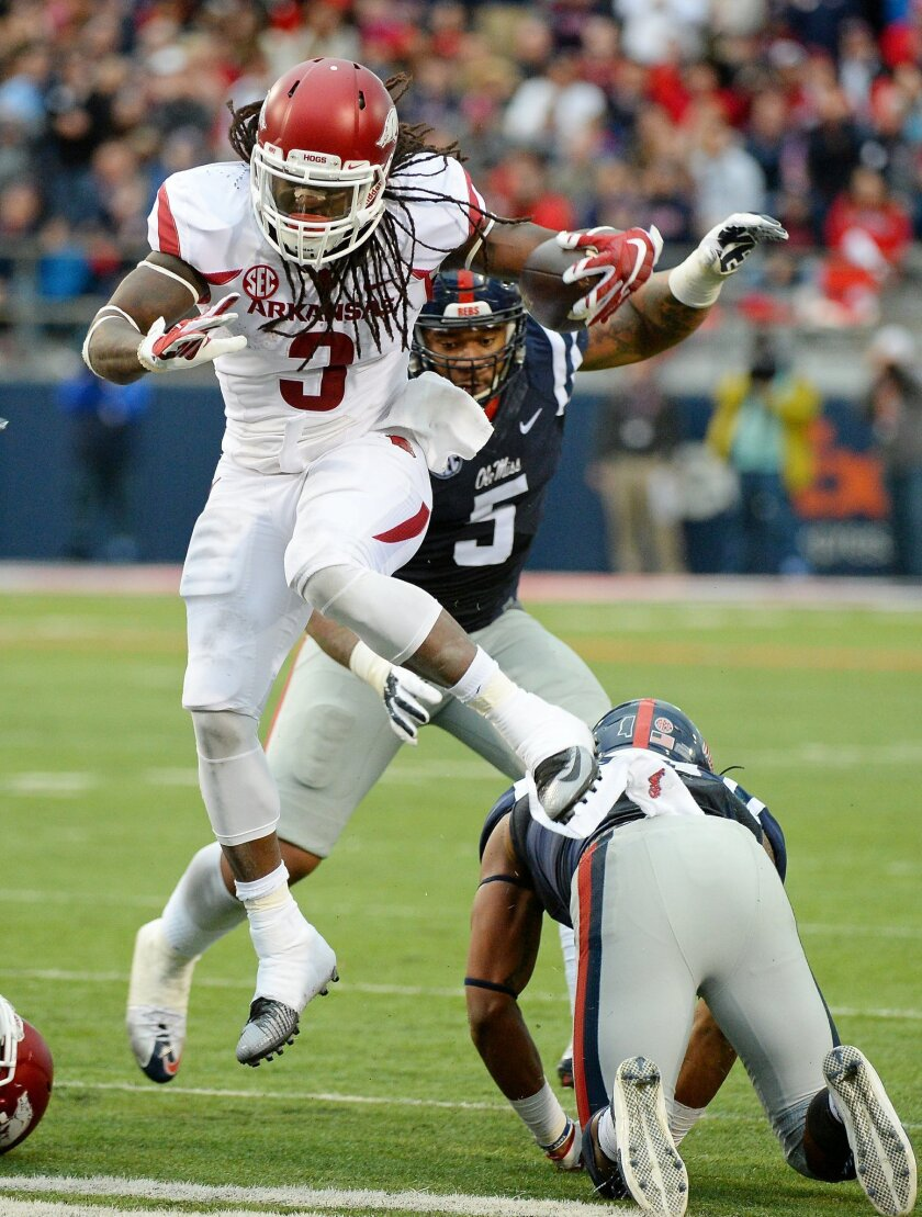Arkansas running back Alex Collins (3) leaps over Mississippi linebacker DeMarquis Gates (31) during the second quarter of an NCAA college football game in Oxford, Miss., Saturday, Nov. 7, 2015. (AP Photo/Thomas Graning)