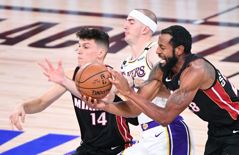 Lakers guard Alex Caruso battles for a loose ball with Miami's Tyler Herro, left, and Andre Iguodala in the third quarter.