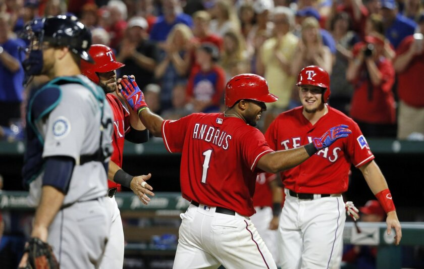 Seattle Mariners catcher Chris Iannetta, left, stands by the plate as Texas Rangers' Mitch Moreland, left rear, Elvis Andrus (1) and Ryan Rua, right rear, celebrate Andrus' three-run home run that scored the duo in the fifth inning of a baseball game, Saturday, June 4, 2016, in Arlington, Texas. (A
