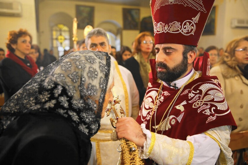 In Damascus, the Syrian capital, a worshiper takes part in a service at the St. Sarkis Church for the Armenian Orthodox in January. The Christmas service also marked the 100th anniversary of the genocide.