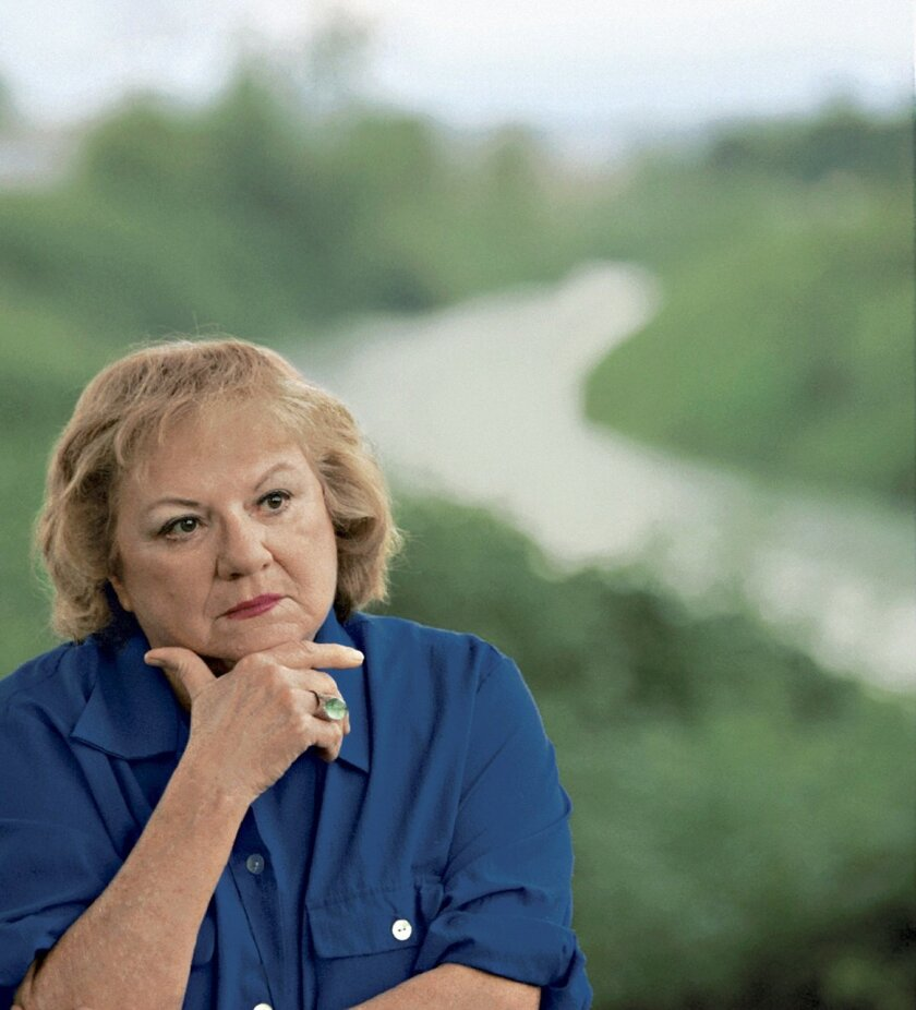 FILE - This July 2004 file photo shows, true-crime author Ann Rule, who wrote a book about serial killer Gary Ridgway, who left some of his victims' bodies along the Green River outside Seattle, Wash., shown in the background. Rule, who wrote more than 30 books, including a profile of her former co-worker, serial killer Ted Bundy, has died at age 83. Scott Thompson, a spokesman for CHI Franciscan Health, said Rule died at Highline Medical Center at 10:30 p.m. Sunday, July 26, 2015. (Betty Udesen/The Seattle Times via AP, File) SEATTLE OUT; USA TODAY OUT; MAGS OUT; TELEVISION OUT; NO SALES; MANDATORY CREDIT TO BOTH THE SEATTLE TIMES AND THE PHOTOGRAPHER