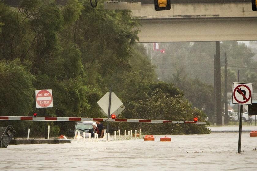 Una mujer no identificada es rescatada de su vehículo, que flota en aguas crecidas hasta la altura de la cintura, en la inundada calle President tras el paso del huracán Matthew junto a la costa este de Georgia, en Savannah, Georgia. (AP Foto/Stephen B. Morton)