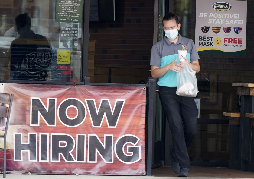 "A customer wearing a face mask passes a ""now hiring"" sign leaving a Richardson, Texas, restaurant with takeout on Sept. 2."