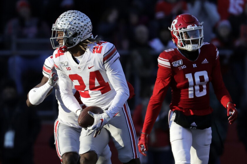 FILE- In this Nov, 16, 2019, file photo, Ohio State cornerback Shaun Wade (24) reacts after making an interception during the first half of an NCAA college football game against Rutgers in Piscataway, N.J. Two of Ohio State's biggest stars, Guard Wyatt Davis and cornerback Shaun Wade, have decided to stay and play football for the Buckeyes this year. (AP Photo/Adam Hunger, File)