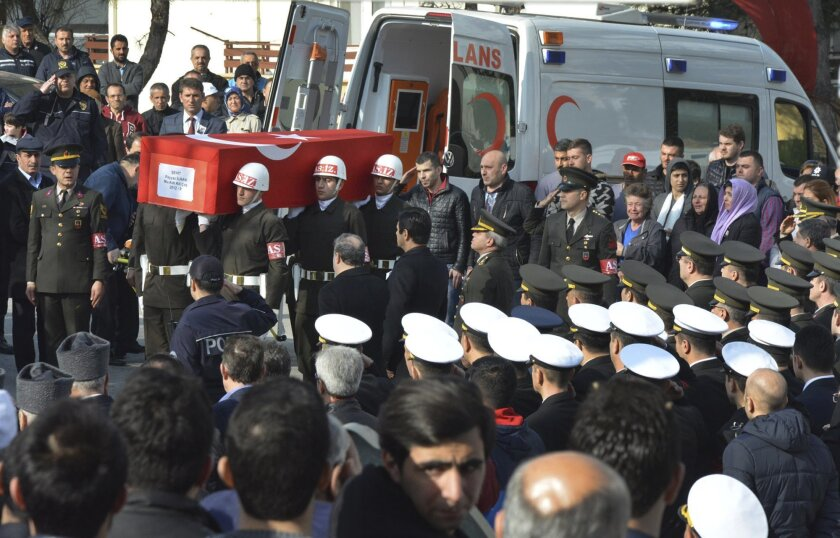 Turkish soldiers carry the national flag-draped coffin of Sergeant First Class Feyyaz Ilhan, killed in Ankara's explosion Wednesday, during his funeral in Bursa,  northeastern Turkey, Thursday, Feb. 18, 2016.  Turkey blamed Kurdish militant groups at home and in neighbouring Syria on Thursday for t