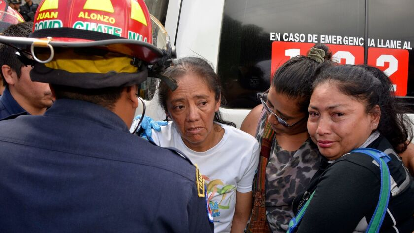 A woman is treated by paramedics near the scene of a fire in San Jose Pinula, Guatemala, on March 8.