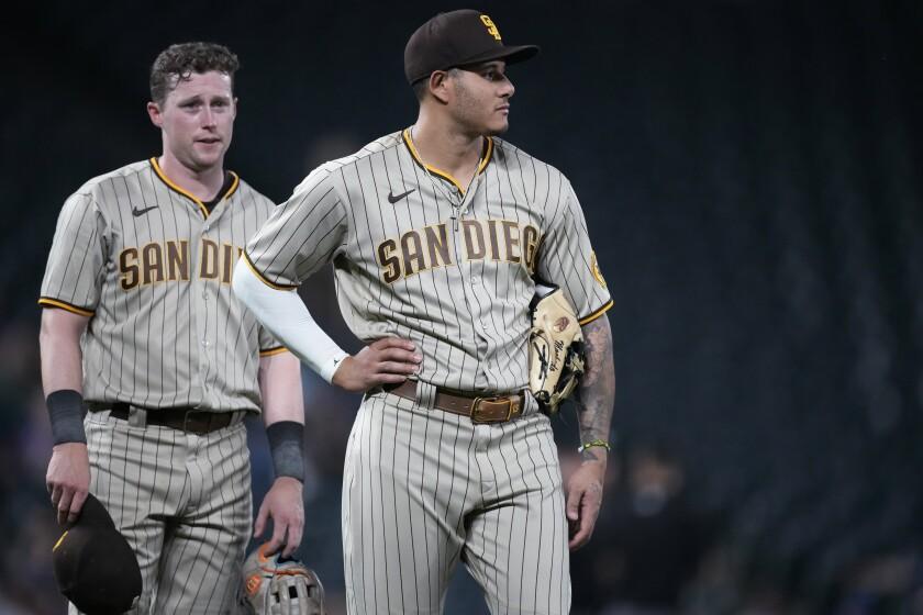Manny Machado, front, and Jake Cronenworth wait for pitching change.