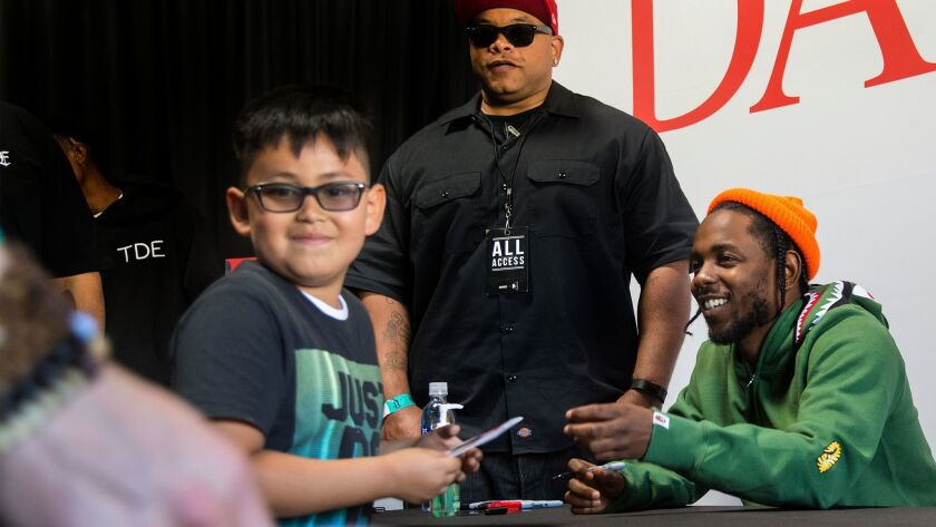 Jonathan Virula, 7, of Bellflower gets an autograph from Kendrick Lamar at a store signing in Compton.