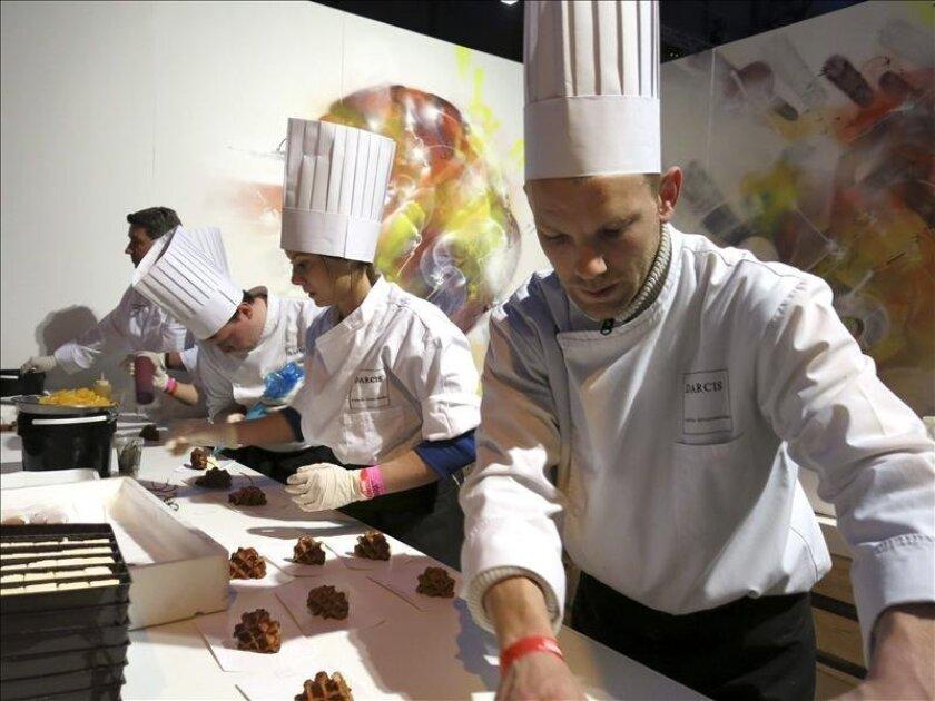 Varios cocineros preparan un postre a base de gofre caliente y chocolate frío en el puesto del pastelero Jean-Philippe Darcis, de la chocolatería Darcis de Verviers (Bélgica) en la feria gastronómica Culinaria que celebra en Bruselas su quinta edición. EFE