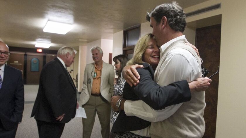 Rita Brandin, senior vice president and development director for Newland Communities, gets a hug from her husband Erik Brandin in the hallway outside of the San Diego County Board of Supervisor's chambers. Her Newland Sierra housing development was approved by a 4-0 vote.