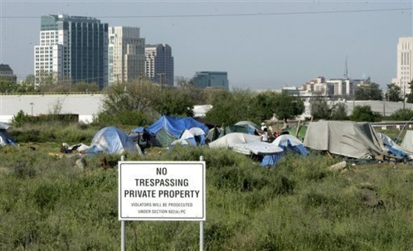 "FILE - In this April 13, 2009 file photo, a ""No trespassing"" sign is seen at the edge of a homeless camp in Sacramento, Calif. (AP Photo/Rich Pedroncelli, File)"