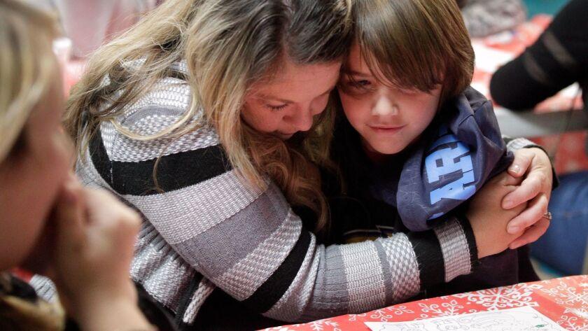 ESCONDIDO, December 5, 2017   Julie Miller hugs her stepson Rhymes Miller, 10, as he writes his lett