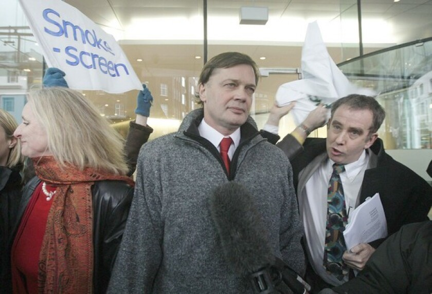 Discredited scientist Andrew Wakefield is show between his wife and a reporter.