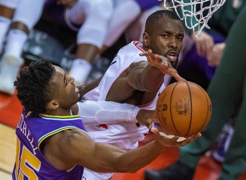 Serge Ibaka (d) de Toronto Raptors detiene un lanzamiento de Donovan Mitchell de Utah Jazz en su partido de baloncesto de la NBA en Toronto, Canadá, el 1 de enero de 2019. EFE