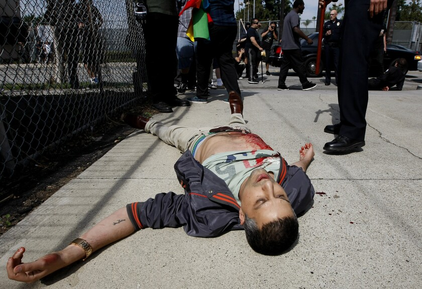 A protester lies on the ground after being stabbed in an altercation with KKK members. Klansmen were once the dominant political force in Anaheim, holding four of five City Council seats before a recall effort led to their ouster in 1924.