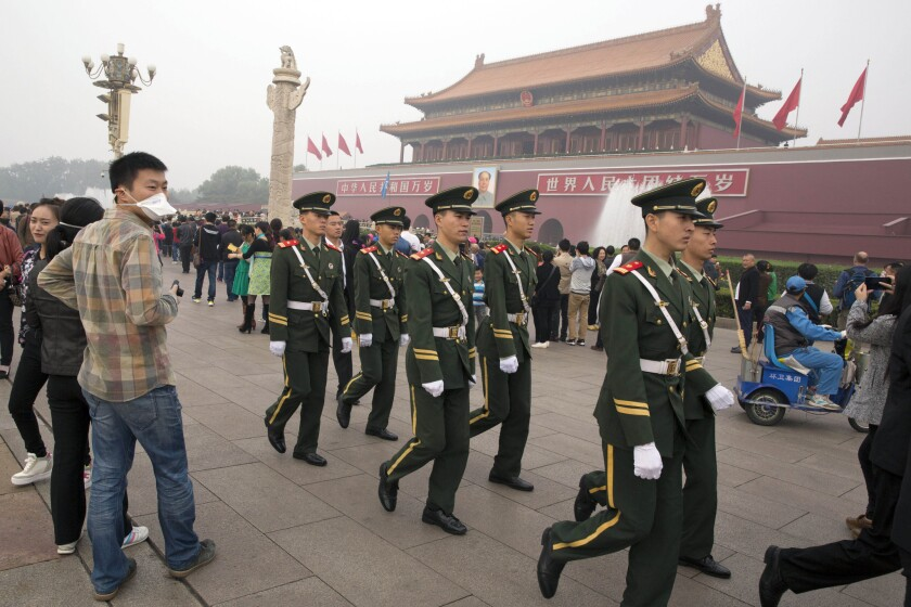 In this Oct. 11 photo, Chinese paramilitary police march across Tiananmen Gate in Beijing.