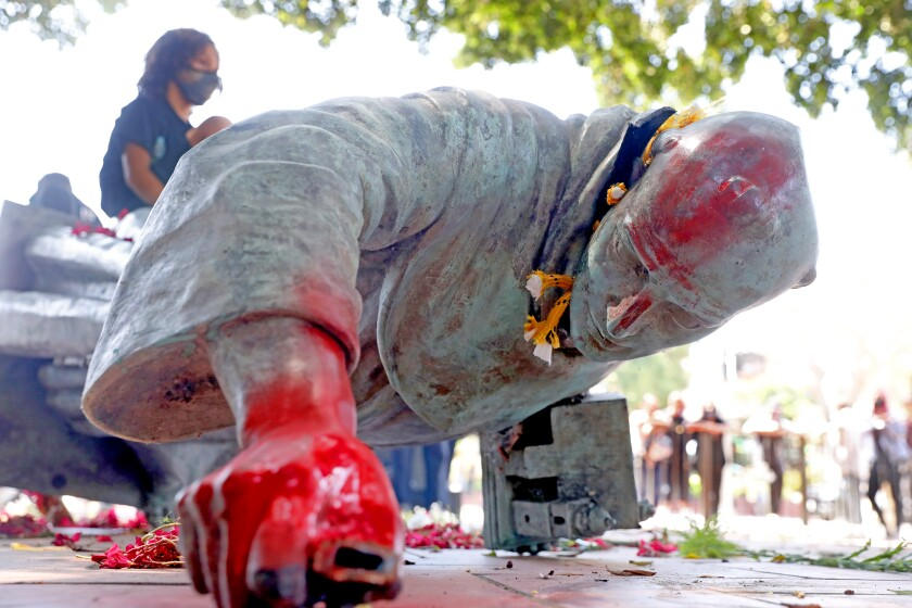 Activists topple and deface with red paint the statue of Father Junipero Serra at Father Serra Park in Los Angeles.