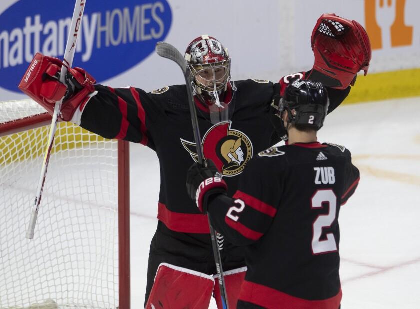 Ottawa Senators goaltender Filip Gustavsson celebrates with defenseman Artem Zub following the final whistle in NHL hockey game action against the Winnipeg Jets in Ottawa, Ontario, Monday, May 3, 2021. (Adrian Wyld/The Canadian Press via AP)