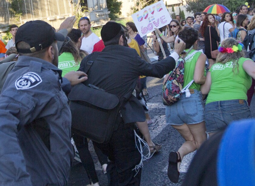 A man later identified as suspect Yishai Shlissel raises a knife at a gay pride parade in central Jerusalem. The girl on the right, with the flowers in her hair, later died of her wounds.