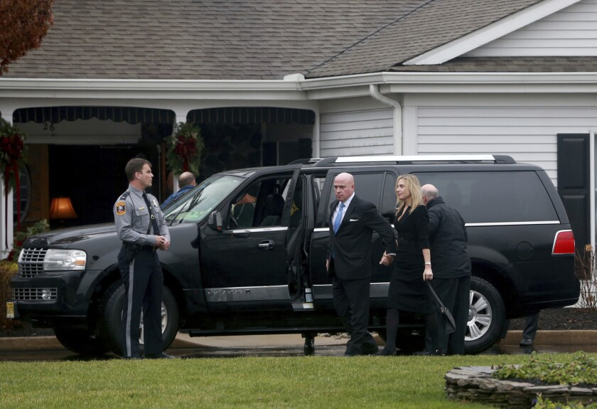 A hearse is parked oiuuside funeral services at the Holmdel Funeral Home in Holmdel, N.J., to mourn Keith Caneiro; his wife, Jennifer, and their two young children, Jesse and Sophia. All were found dead Nov. 20 at their Colts Neck mansion.