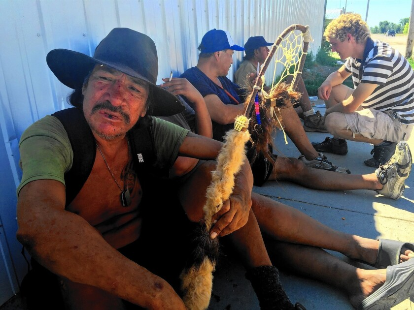 Harley Dreamer lives on the streets of Whiteclay, Neb. He says he is a descendant of Crazy Horse, but he's unable to quit drinking. Abram Neumann, 20, at right, talks to men sitting with Dreamer.