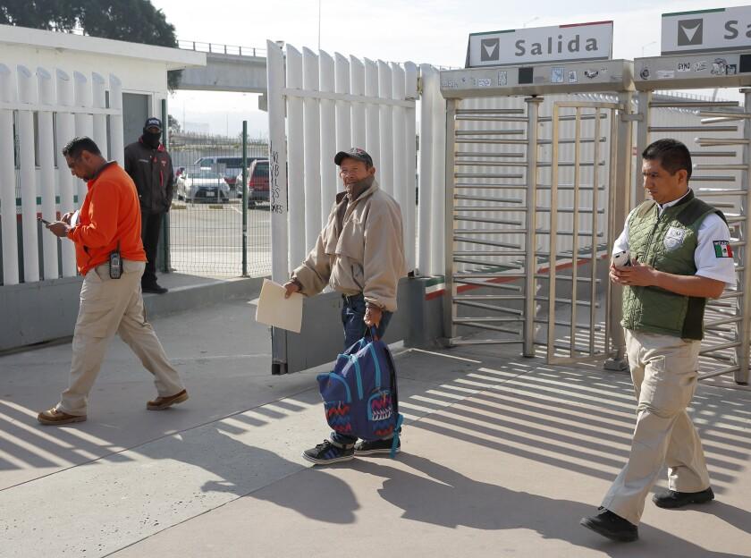 Migrant Carlos Catarldo Gomez, of Honduras, center, is escorted by Mexican officials