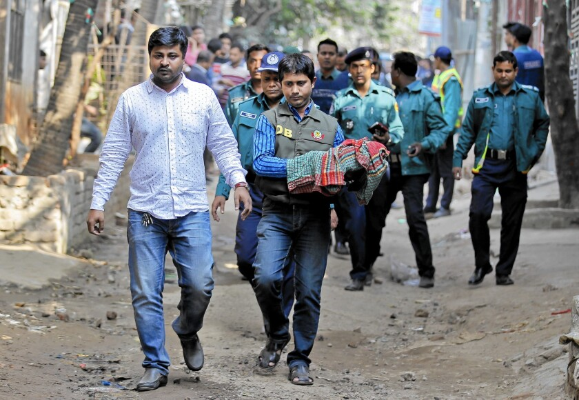 A member of a bomb disposal unit carries away homemade bombs during a raid on a building where members of a banned Islamist group were detained in Dhaka, Bangladesh, in December 2015.