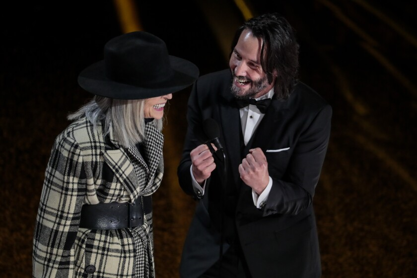 Keanu Reeves, in a tux, and Diane Keaton laugh onstage.