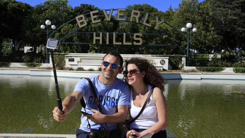 Sevag and Houry Alsanian, tourists from Lebanon, take photos in front of the Beverly Hills sign in Beverly Gardens Park on Oct. 30, 2015. The Beverly Hills Conference & Visitors Bureau is proposing a tour bus stop in the city's business district.
